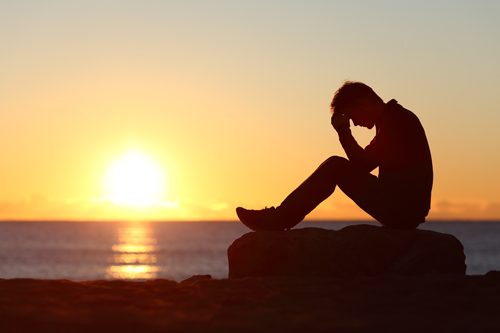 How to Recognize Addiction in Your Loved One - man sitting on beach - mountain laurel recovery center