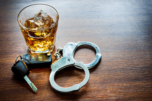 glass of liquor next to car keys and handcuffs - dui