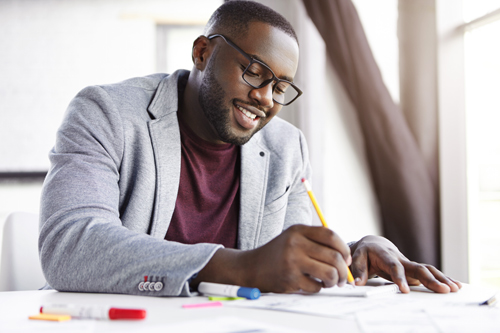 handsome African American man smiling and making notes in planner or notebook - goals