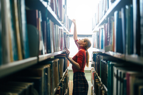 woman reaching for book on library shelf - ideas