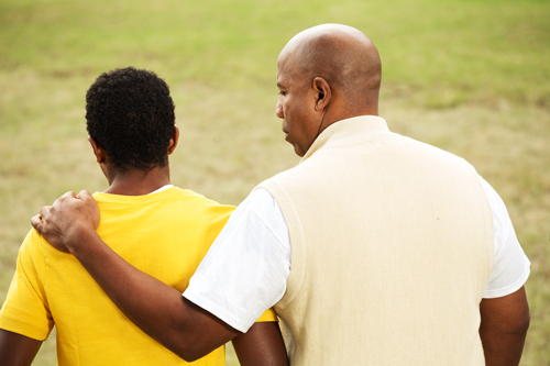 African American dad with arm around teenage son - view from behind them - teen