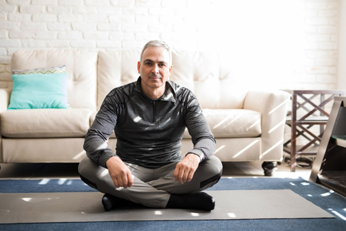 middle age man sitting on exercise mat at home - exercise