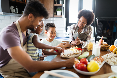 beautiful African American family cooking a healthy meal together - relationships