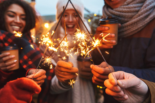young adult friends using sparklers outdoors in cold weather - holiday season
