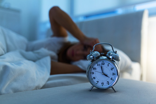 woman suffering from insomnia laying awake in bed with alarm clock showing 4 - Ambien addiction