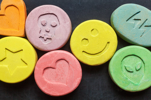 closeup of colorful tablets with imprints of hearts, stars, and smiley faces - ecstasy - mdma