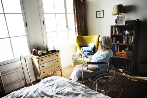 woman in her seventies in a wheelchair looking out a bedroom window - loneliness and addiction